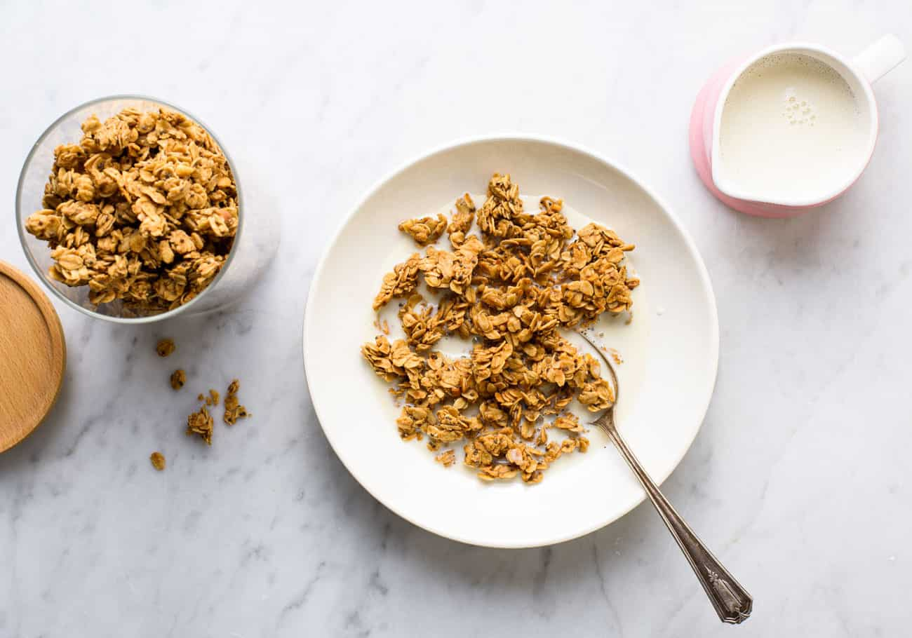 Peanut butter granola in a white bowl on a marble table next to a pink milk pourer