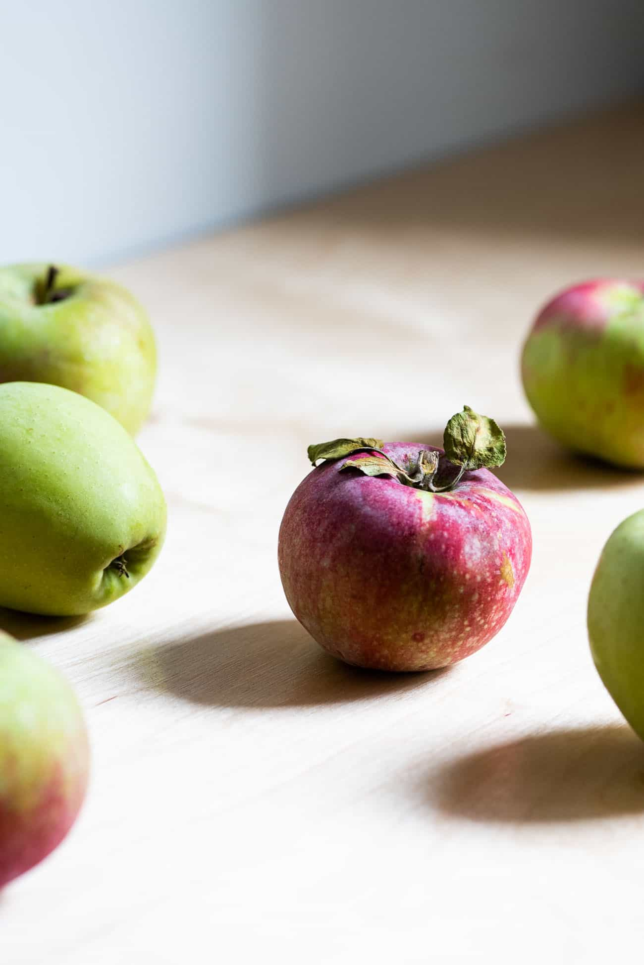 Green and red apples on a wooden kitchen counter