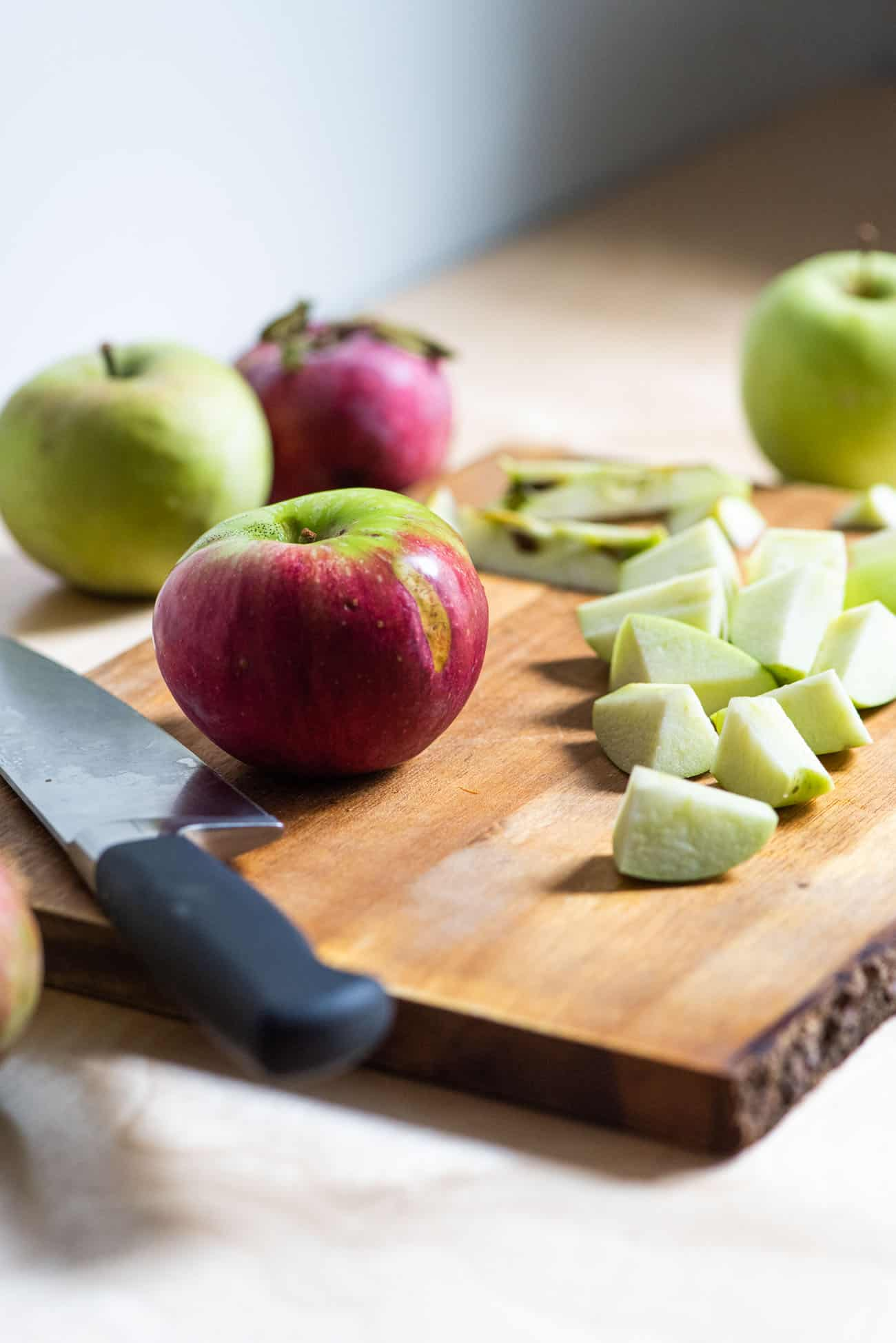Chopped apples on a cutting board on a wooden kitchen counter