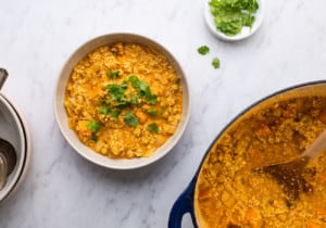 A bowl of cauliflower rice curry next to a Dutch oven and a saucer with cilantro