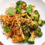 A crispy tofu bowl with brown rice, charred broccoli, and peanut sauce