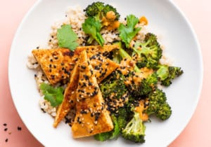 A crispy tofu bowl with brown rice, charred broccoli, and peanut sauce