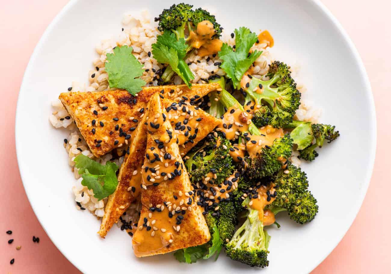 A crispy tofu bowl with brown rice, charred broccoli, and peanut sauce.