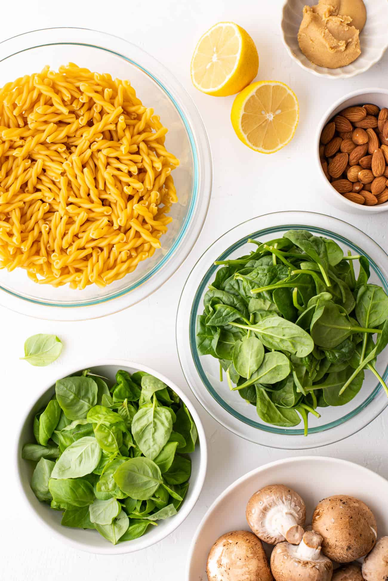 Ingredients gathered to make vegan spinach pesto pasta: gemelli, miso, almonds, spinach, basil, and mushrooms