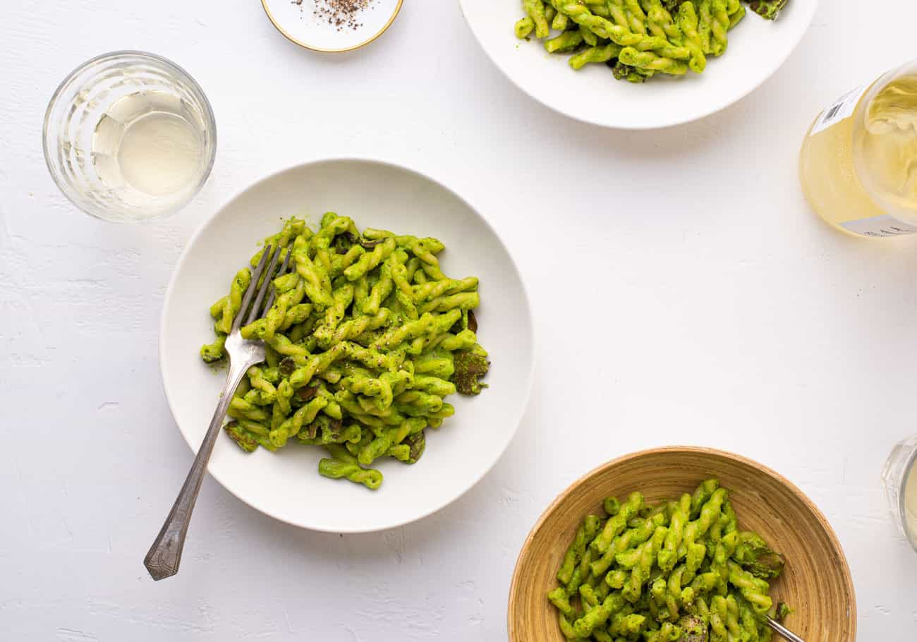 3 bowls of vegan spinach pesto pasta on a white table with white wine