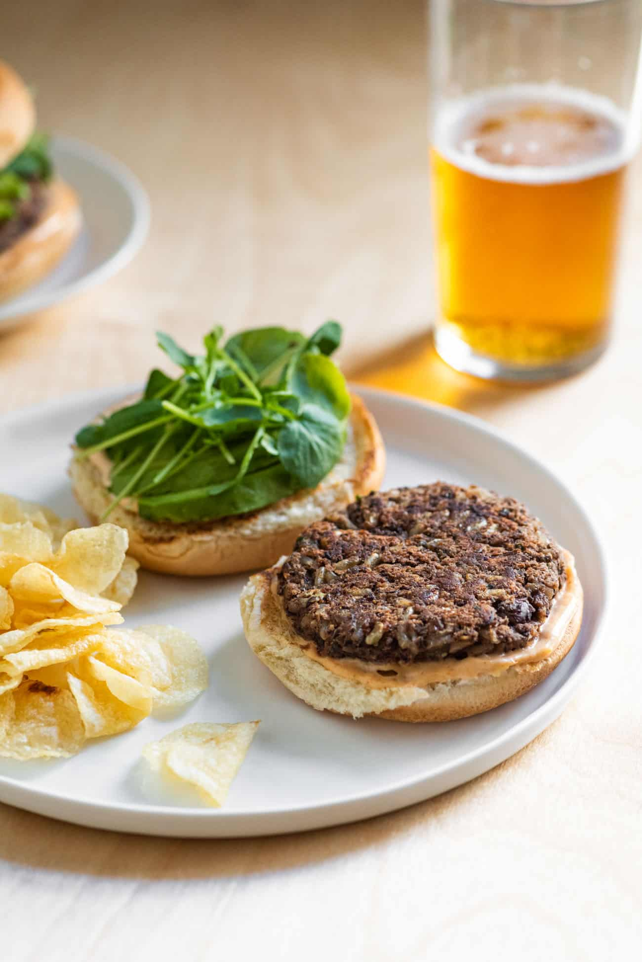 An open-faced vegan black bean burger with watercress, with potato chips on the side and a glass of beer
