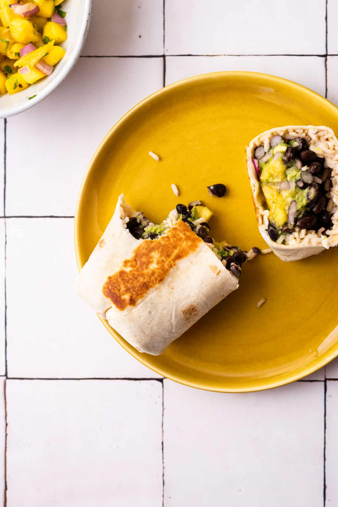 Vegan black bean burrito with mango salsa, cut in half, on a yellow plate on a white-tiled table