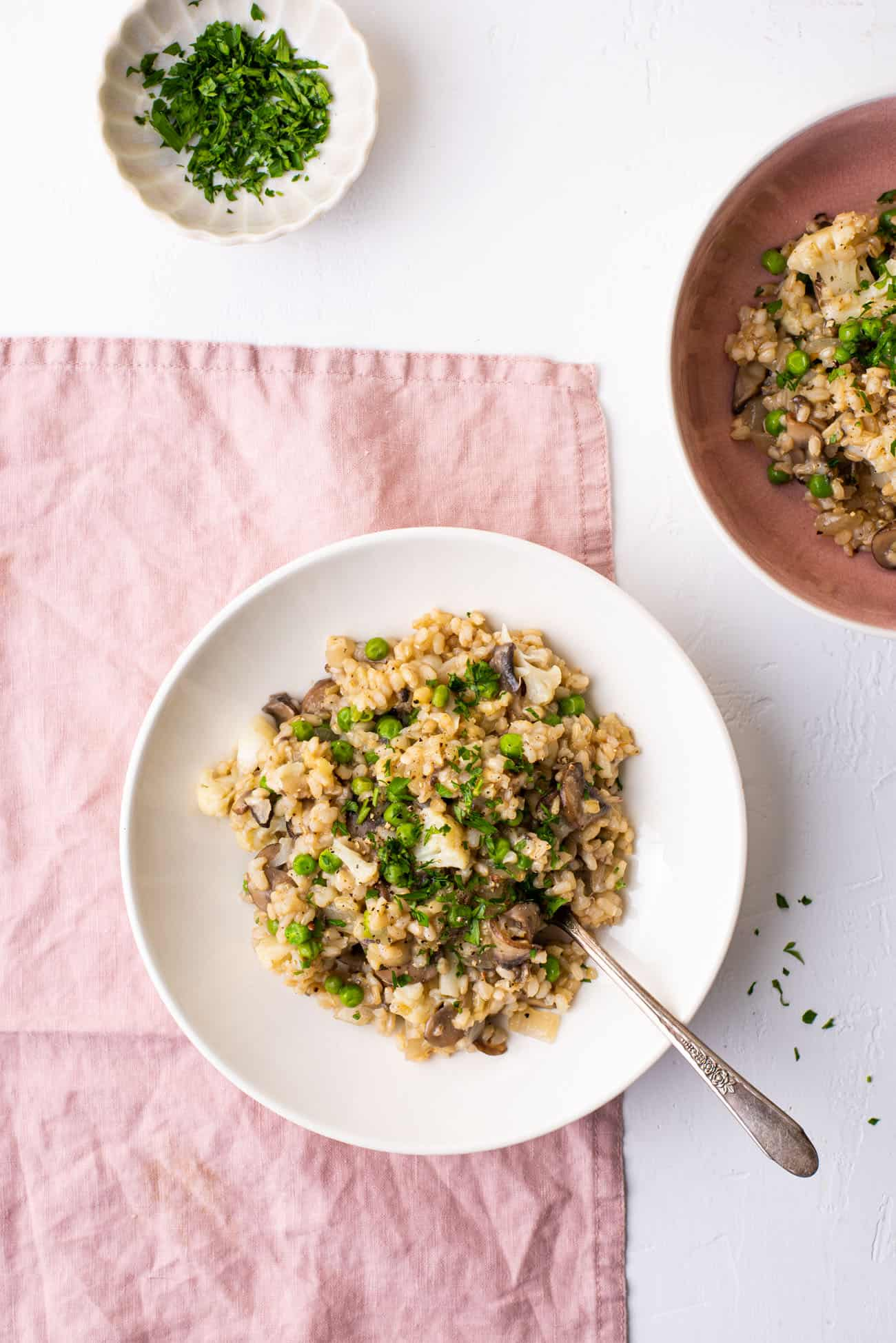 2 bowls of Vegan Mushroom Risotto with Cauliflower and Peas on a pink tablecloth, sprinkled with parsley