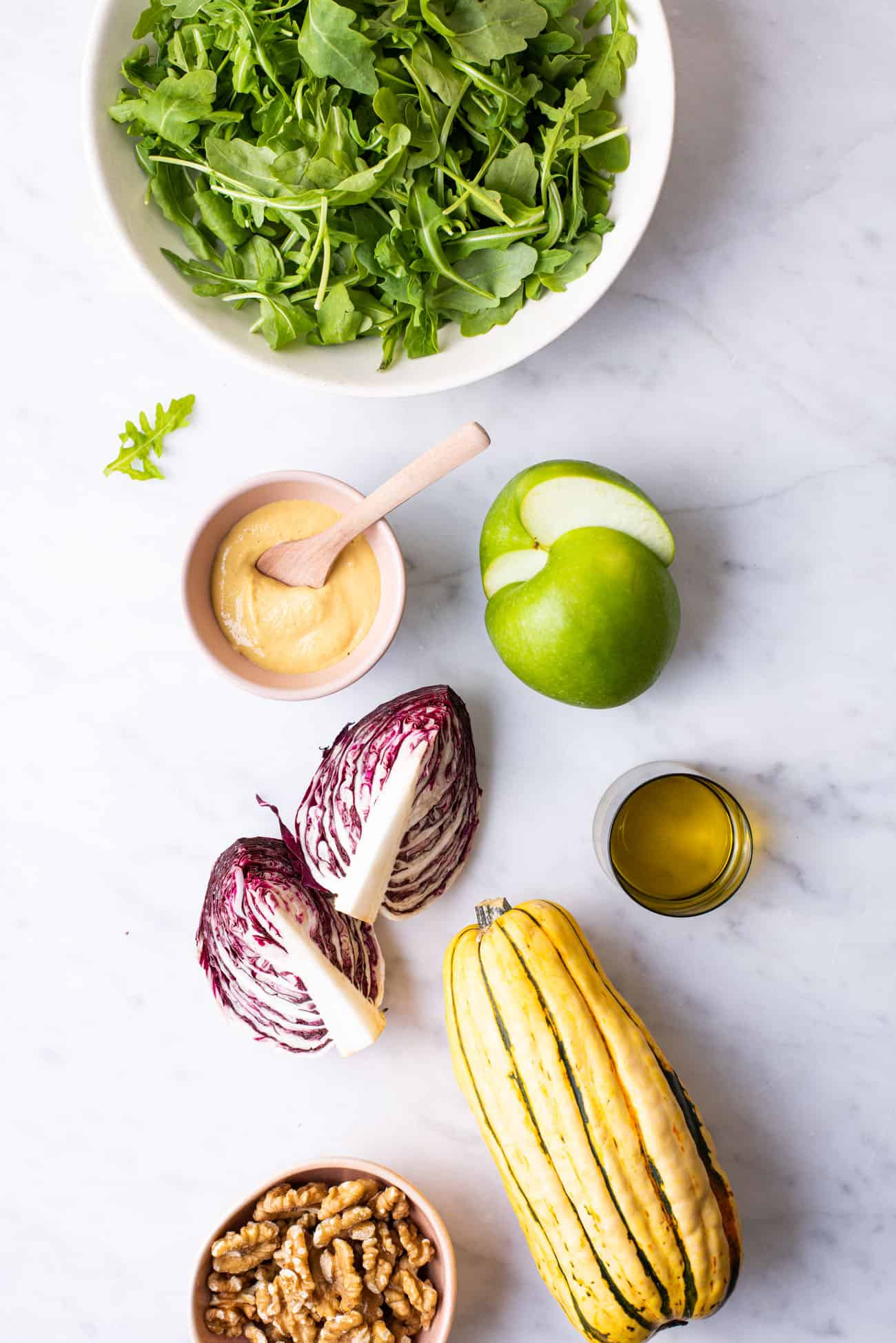 Ingredients to make a Thanksgiving salad arranged on a marble counter: arugula, radicchio, apple, delicata squash, mustard, and walnuts