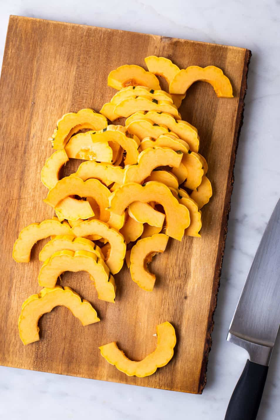 Slices of raw delicata squash on a wooden cutting board