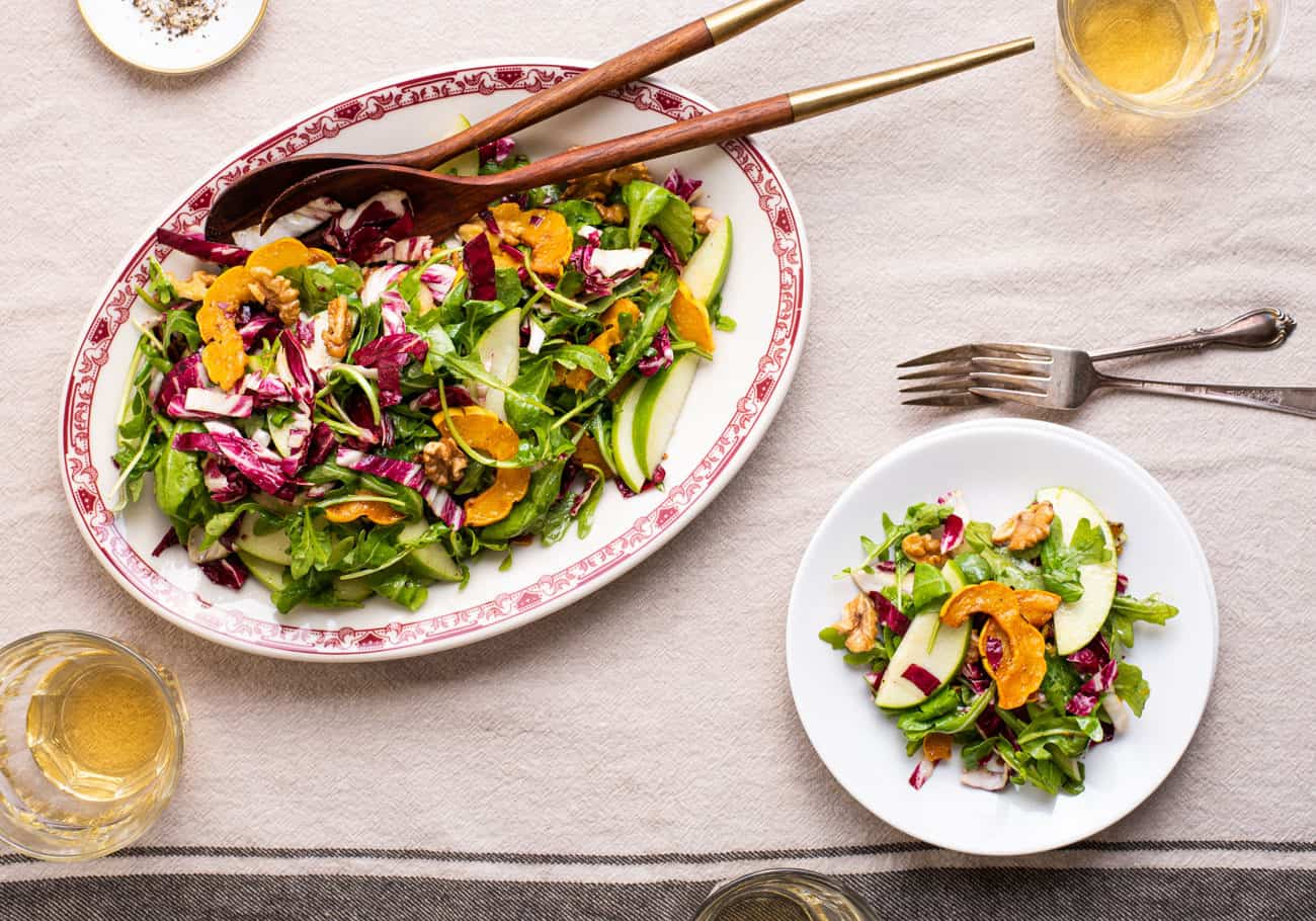 Arugula radicchio salad with delicata squash on an oval platter next to a stack of plates on a beige tablecloth
