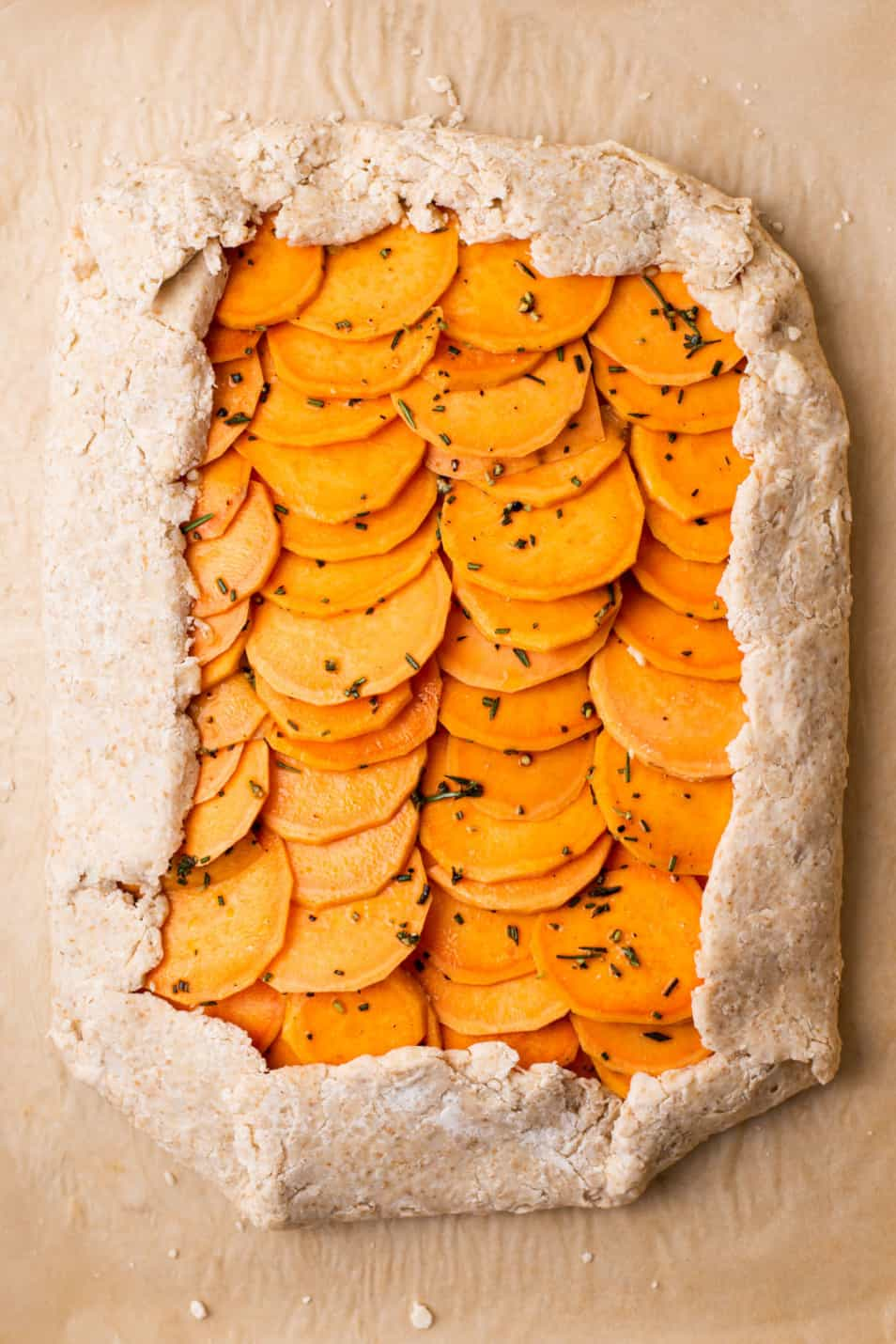 Raw sweet potato galette on brown parchment paper, ready to bake