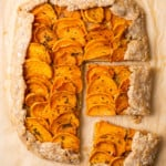 Rectangular vegan sweet potato galette with cashew ricotta on brown parchment paper cut into slices