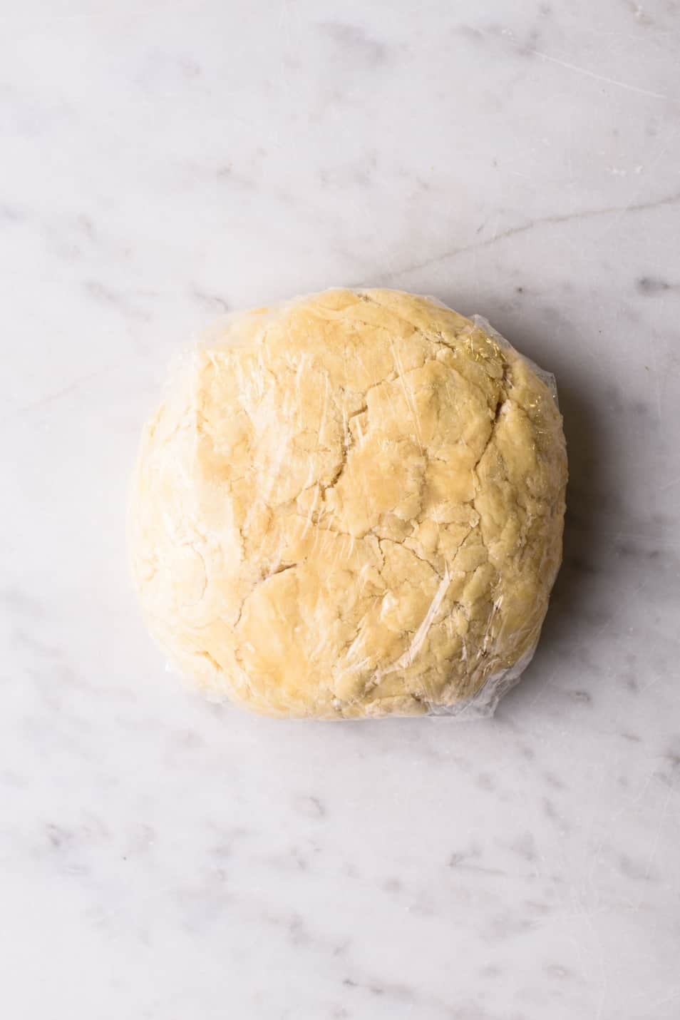 Vegan pie crust dough, shaped into a disc and wrapped in plastic, on a marble counter