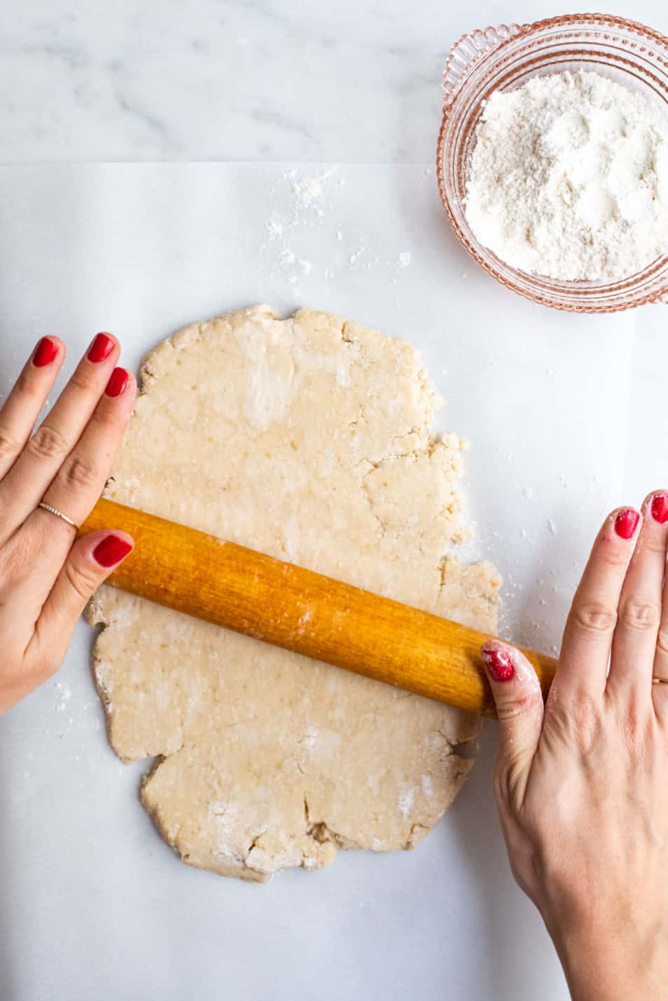 Woman's hands rolling out tart dough