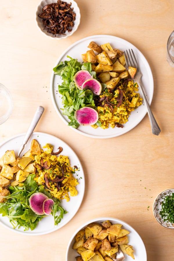 2 plates with tofu scramble, roasted potatoes, and arugula salad on a light wood table