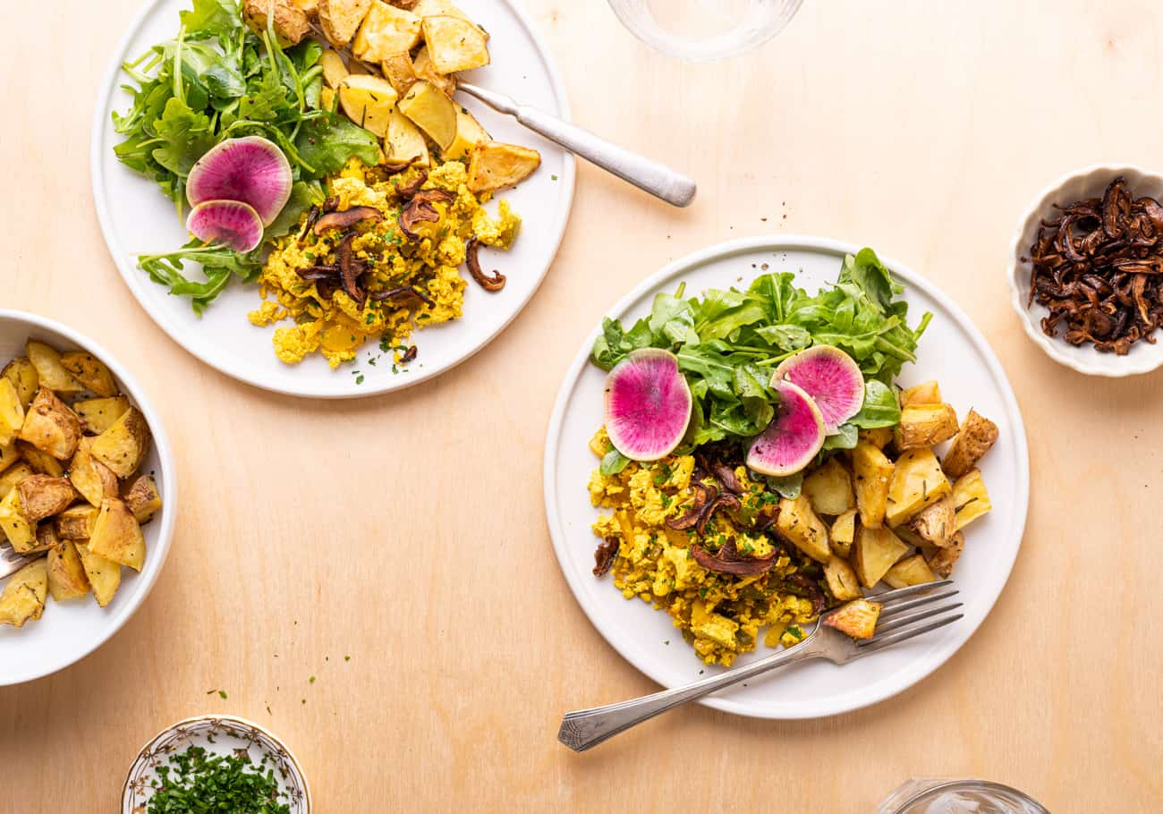 2 plates with tofu scramble, roasted potatoes, and arugula salad on a light wood table