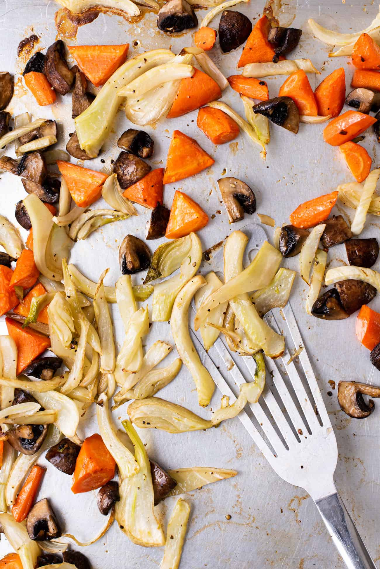 Roasted carrots, fennel, and mushrooms on a baking sheet