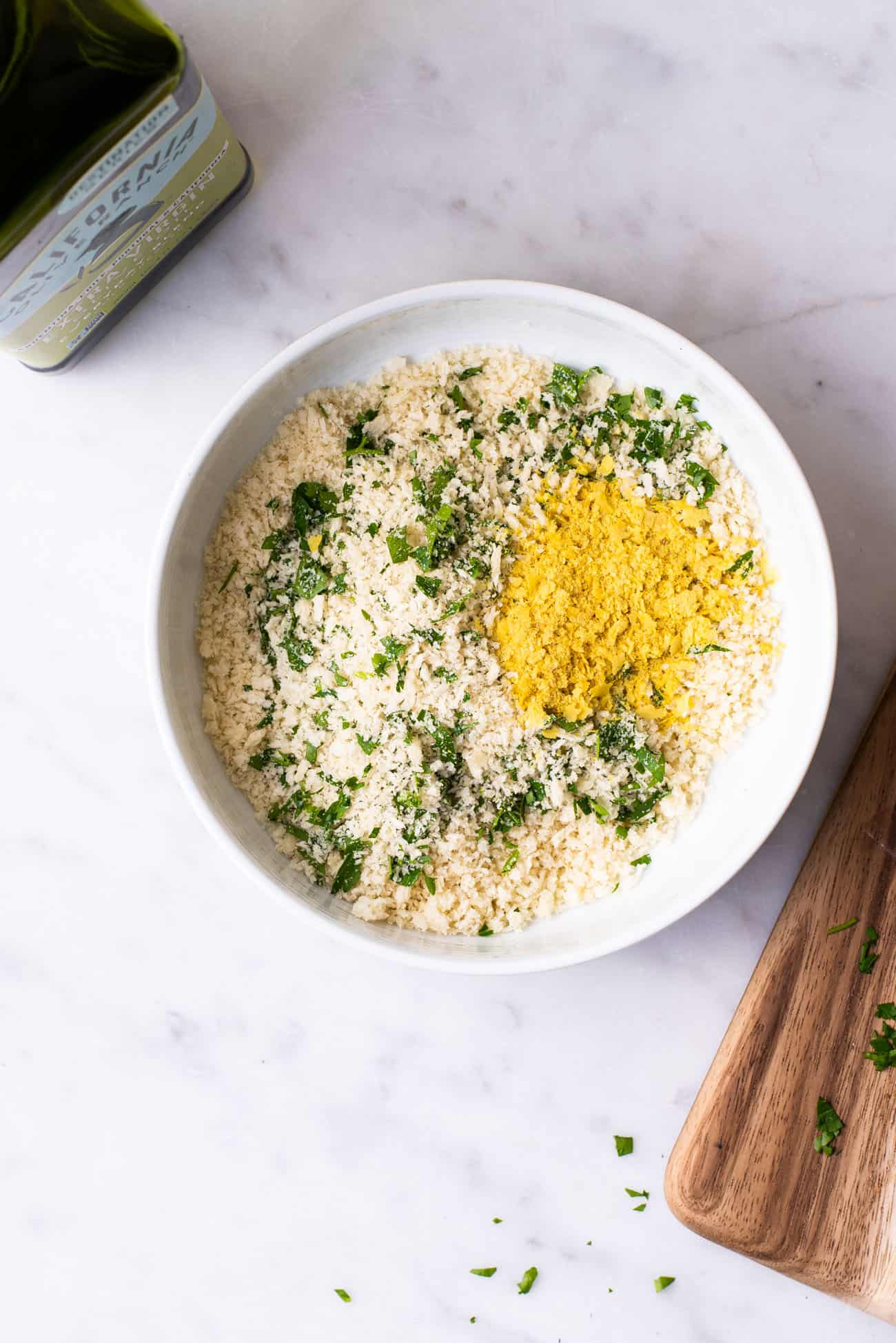 Panko breadcrumbs with nutritional yeast and chopped parsley in a white bowl next to a bottle of olive oil