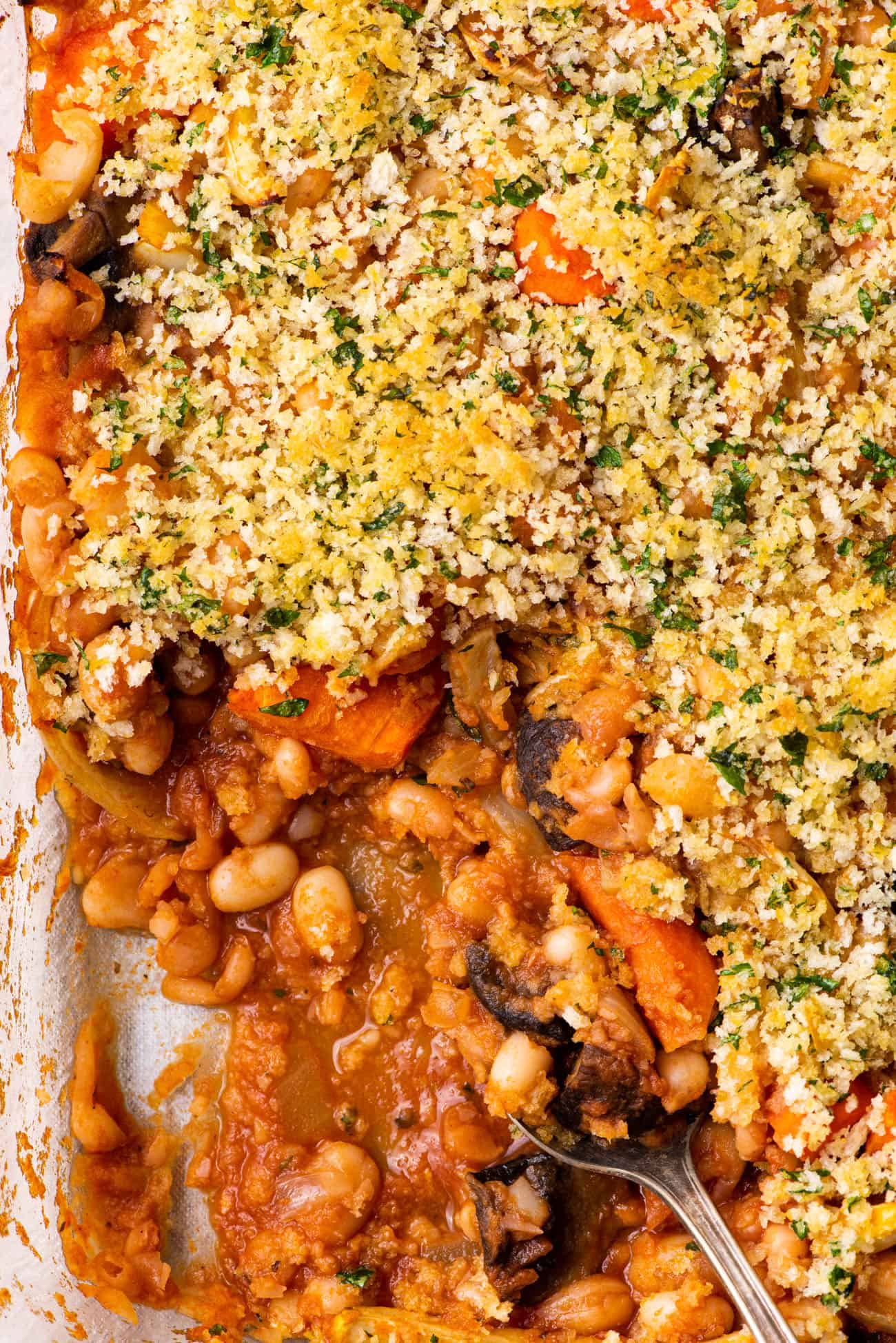 Close-up of cassoulet with brothy beans, roasted vegetables, and golden breadcrumbs