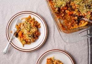 A glass Pyrex pan of vegan cassoulet next to 2 ceramic plates on a beige tablecloth