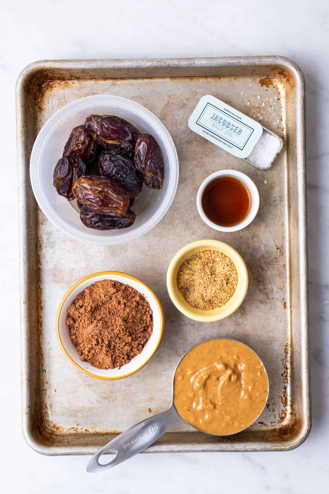 Medjool dates, cocoa powder, peanut butter, flax, and vanilla - gathered on a metal tray