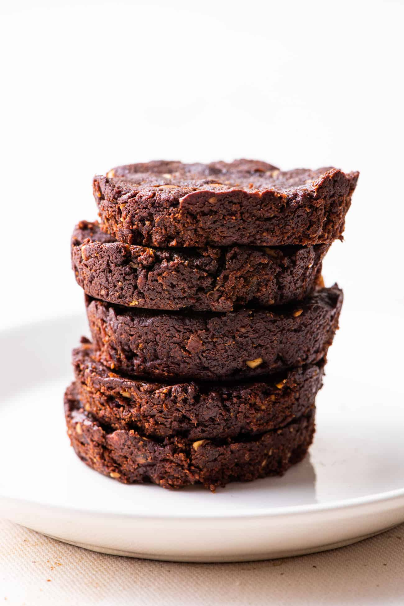Stack of round sugar-free date brownies on a white plate