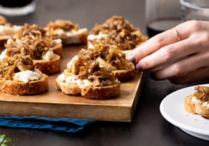 Balsamic caramelized onion crostini on a wooden board next to glasses with red wine