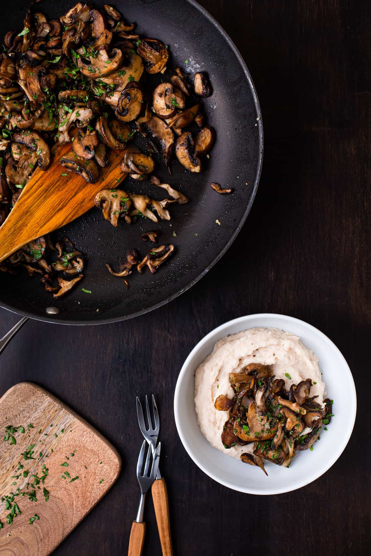 Sauteed mushrooms in a skillet next to a white bowl and chopped parsley, on a dark wooden table