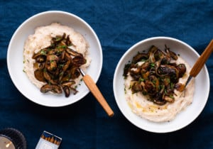 2 bowls of white bean puree topped with garlic sauteed mushrooms on an indigo tablecloth next to a candle and wine classes