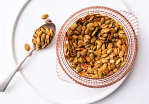 Spiced pumpkin seeds in a pink glass bowl on a white ceramic plate