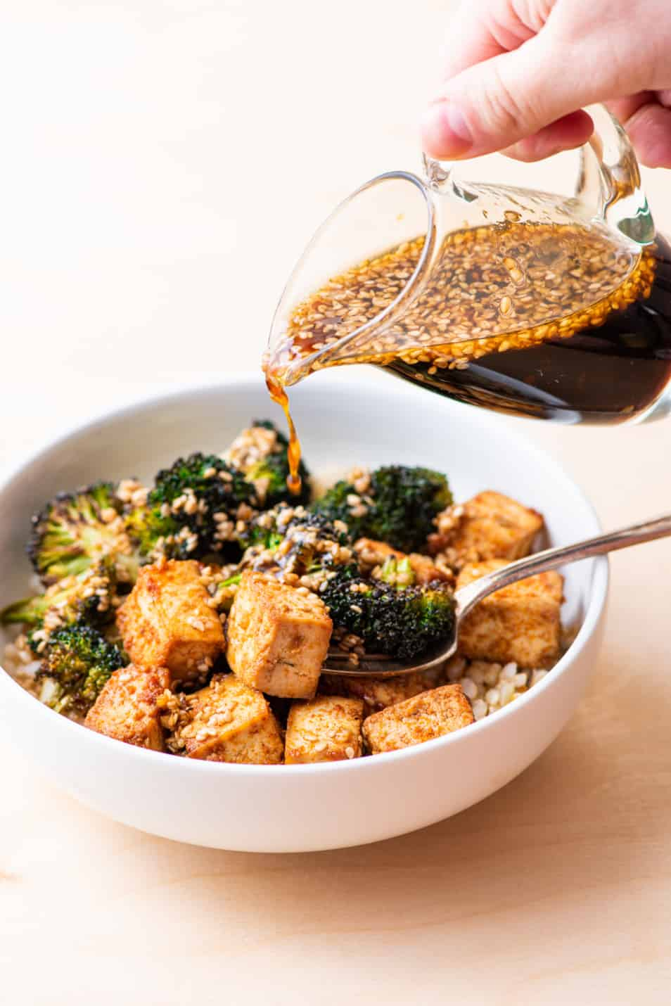 Sesame dressing in a glass pourer, being poured on a tofu grain bowl