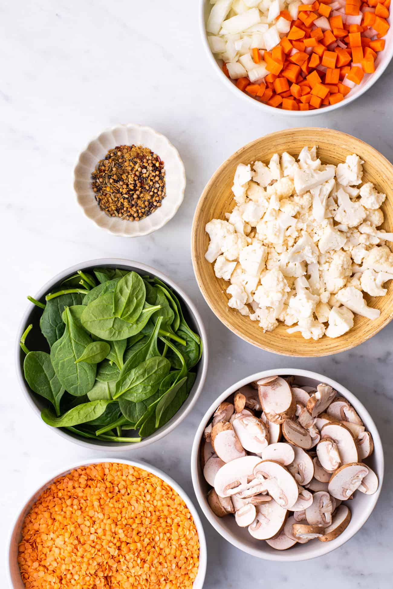 Ingredients gathered to make red lentil dal: onion, carrot, spices, cauliflower, spinach, mushrooms, and lentils