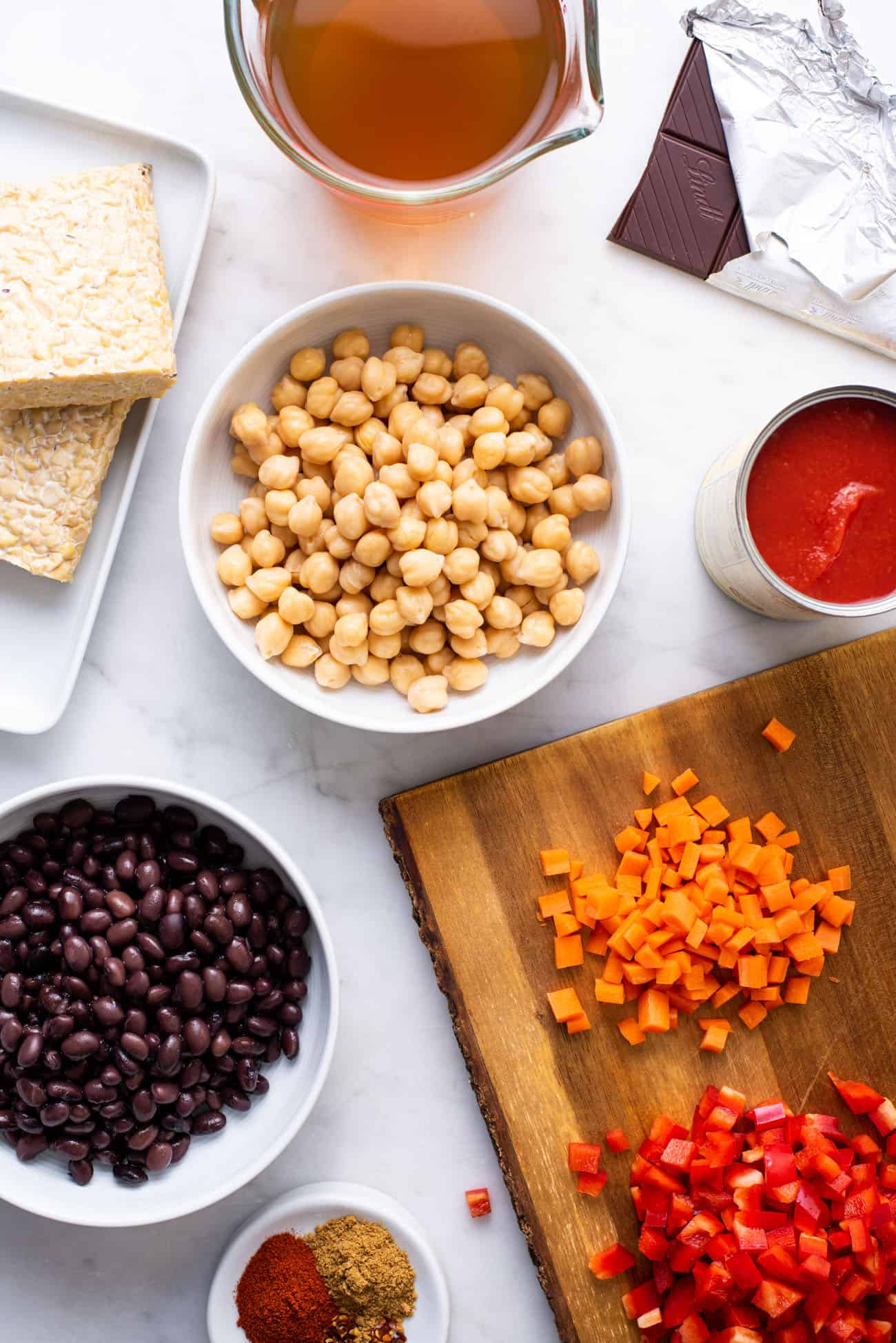 Ingredients gathered to make tempeh chili: chickpeas, black beans, dark chocolate, carrots, bell pepper
