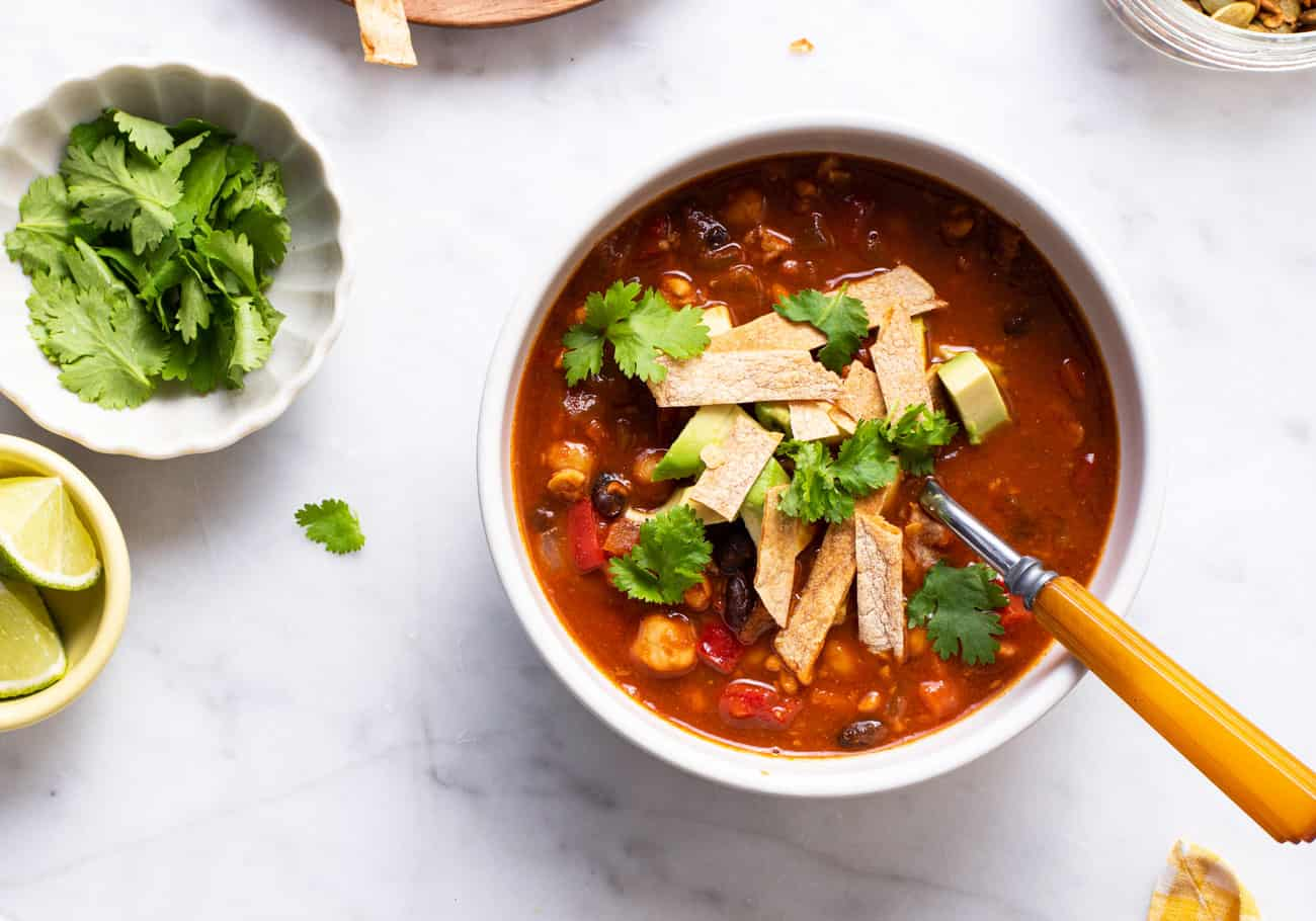 A bowl of tempeh chili on a marble table, garnished with avocado, tortilla strips, and cilantro