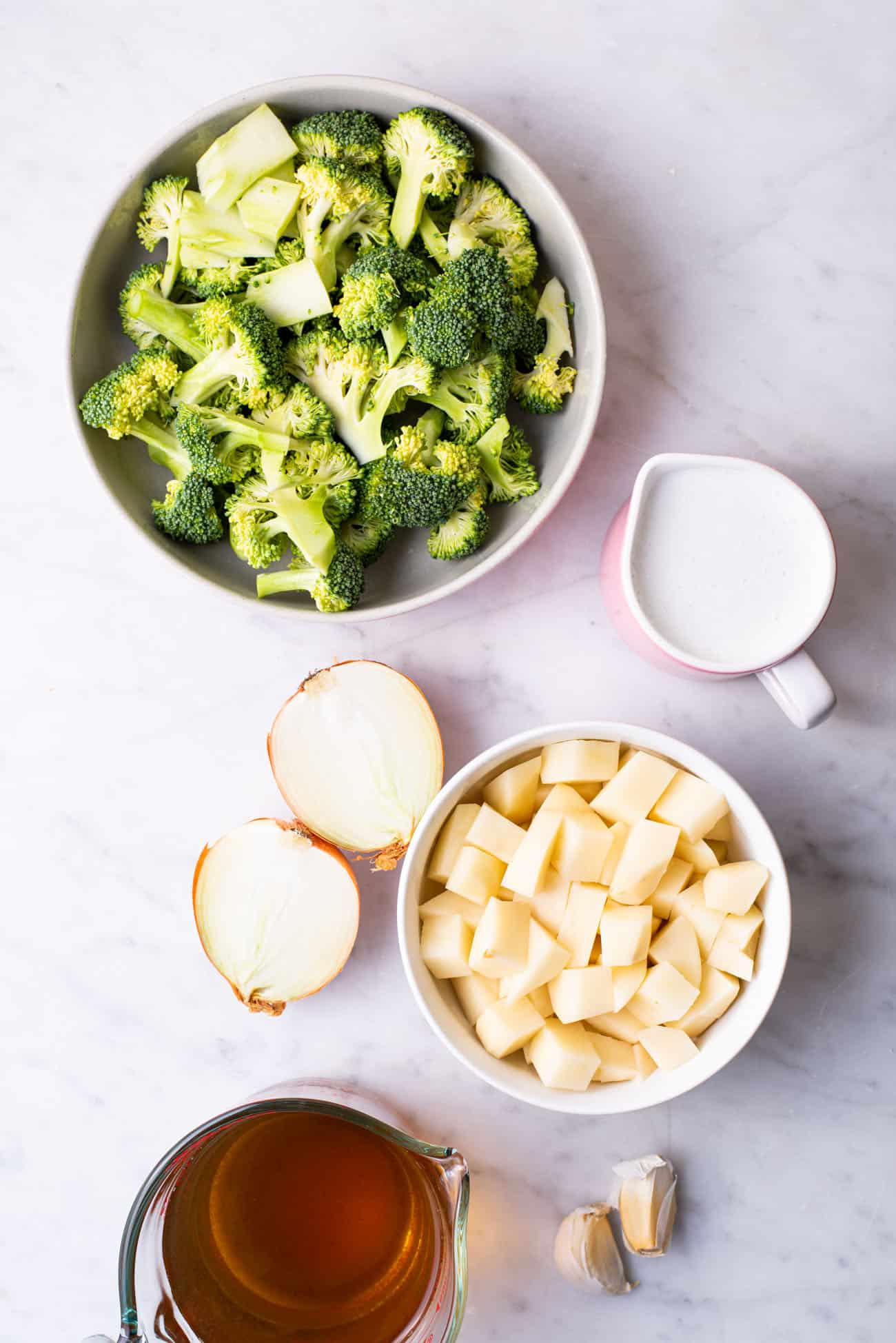 Ingredients gathered to make creamy broccoli soup: broccoli, onion, potato, almond milk, and vegetable broth
