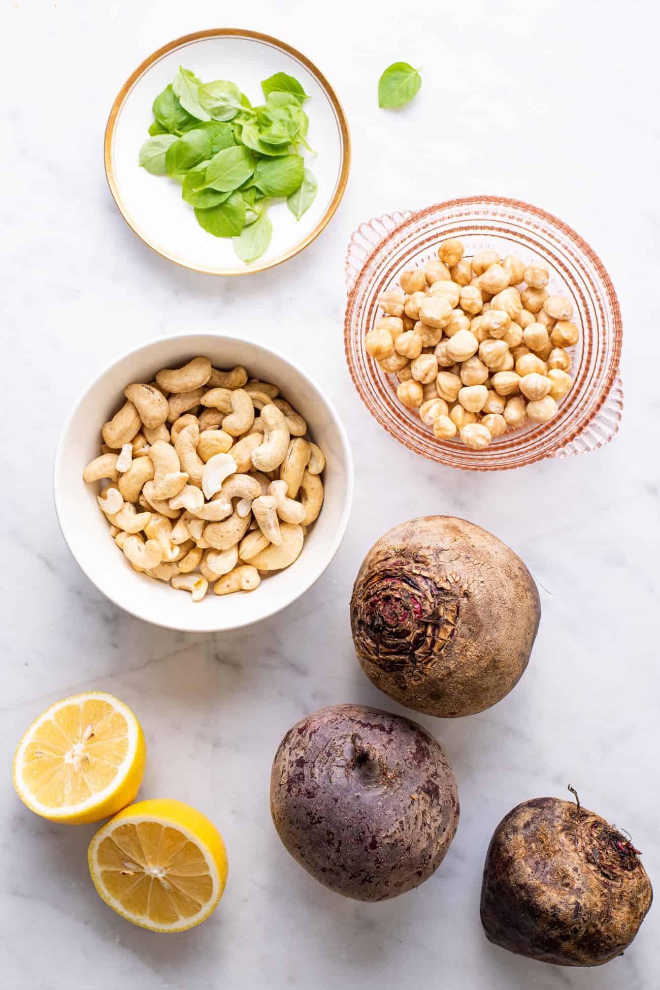 Basil, cashews, hazelnuts, lemon, and beets, gathered on a marble table