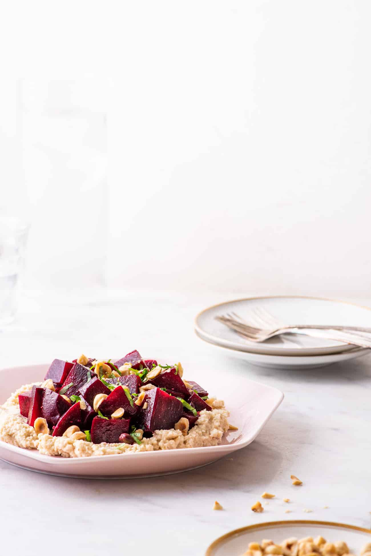 Marinated beets with cashew ricotta on a pink plate on a marble table next to a dish with chopped hazelnuts