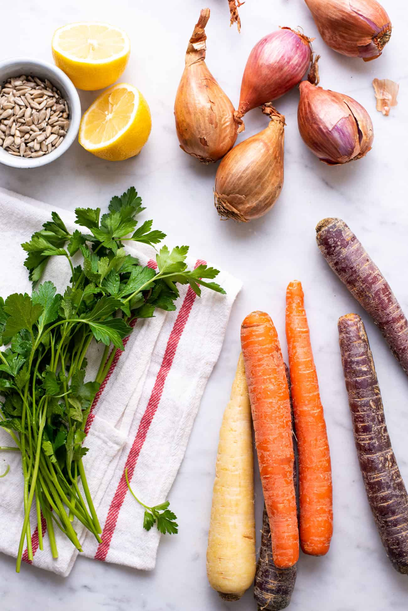 Parsley, sunflower seeds, lemon, carrots, and shallots gathered on a marble table