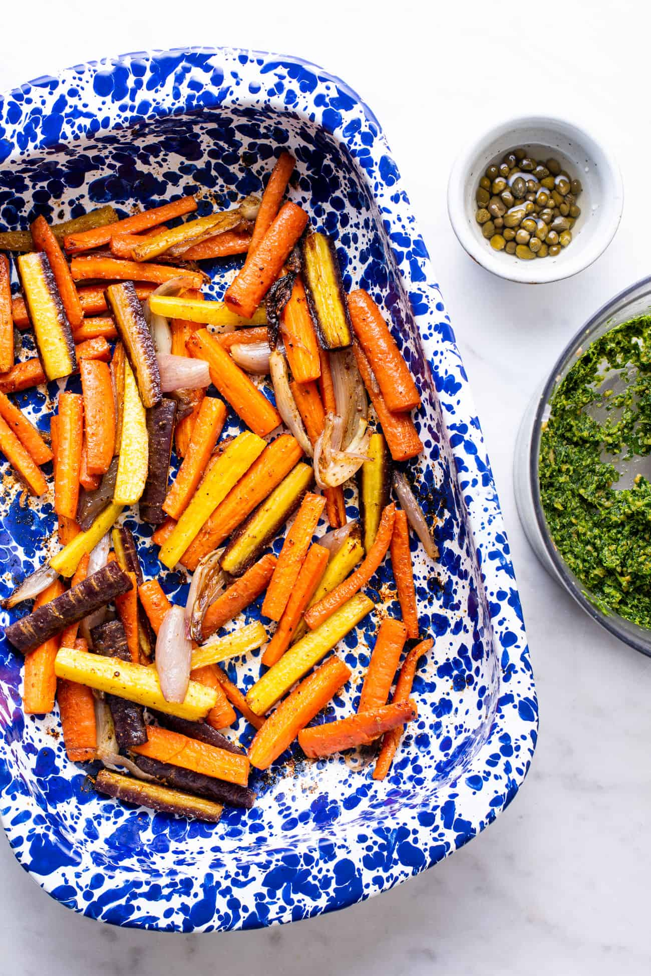 Roasted carrots and shallots in a blue speckled roasting pan next to pesto and capers