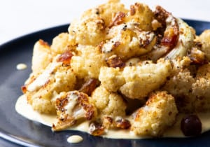 Crispy roasted cauliflower with tahini sauce and chopped dates on a dark blue plate