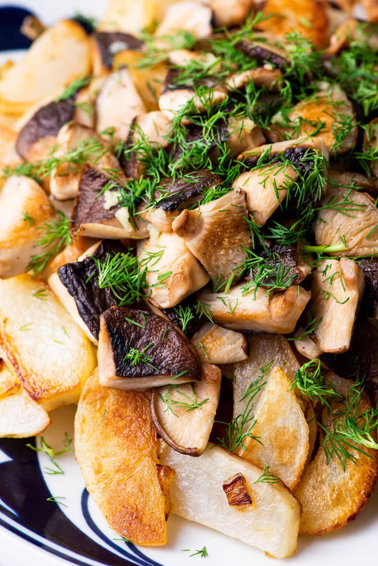 Close-up of Russian fried potatoes with shiitake mushrooms and dill