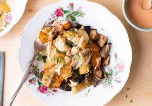 Russian fried potatoes with shiitake mushrooms and dill, on a floral plate, on a wooden table