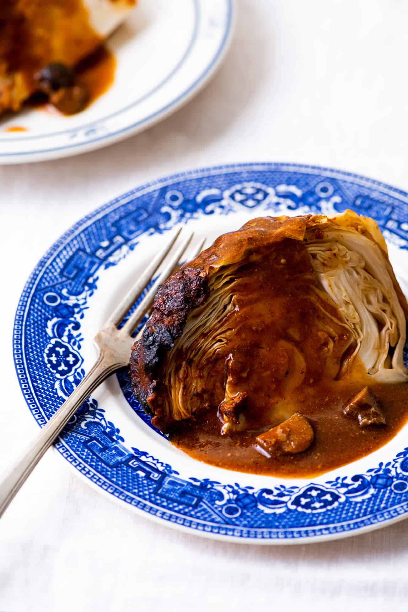 A wedge of whole roasted cabbage with a mushroom-tomato gravy drizzled on top, on a blue chinoiserie plate