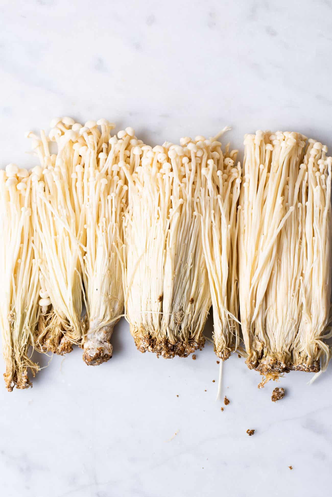 Raw enoki mushrooms on a marble table