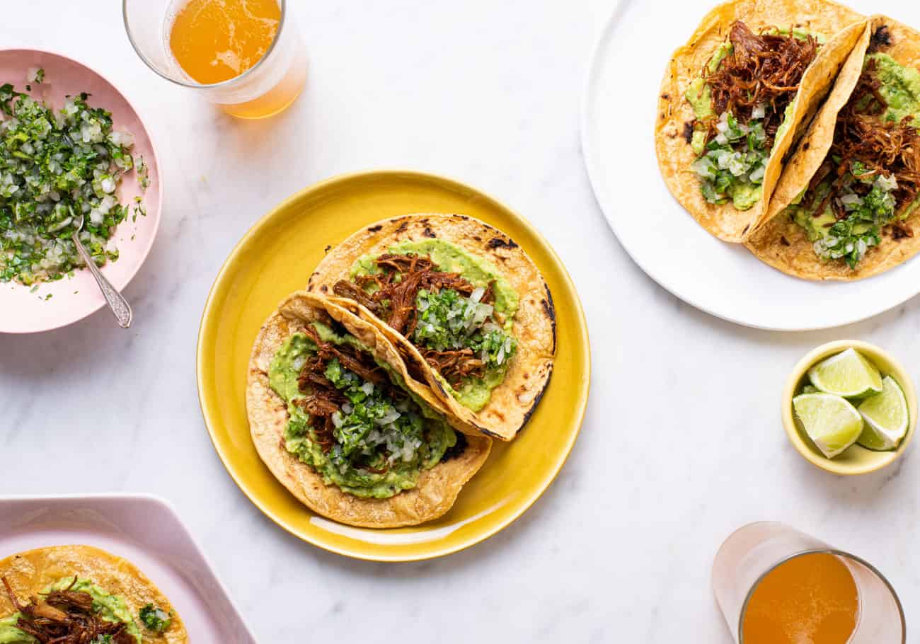 Vegan carnitas tacos on various plates, next to glasses of beer and cilantro-onion relish.