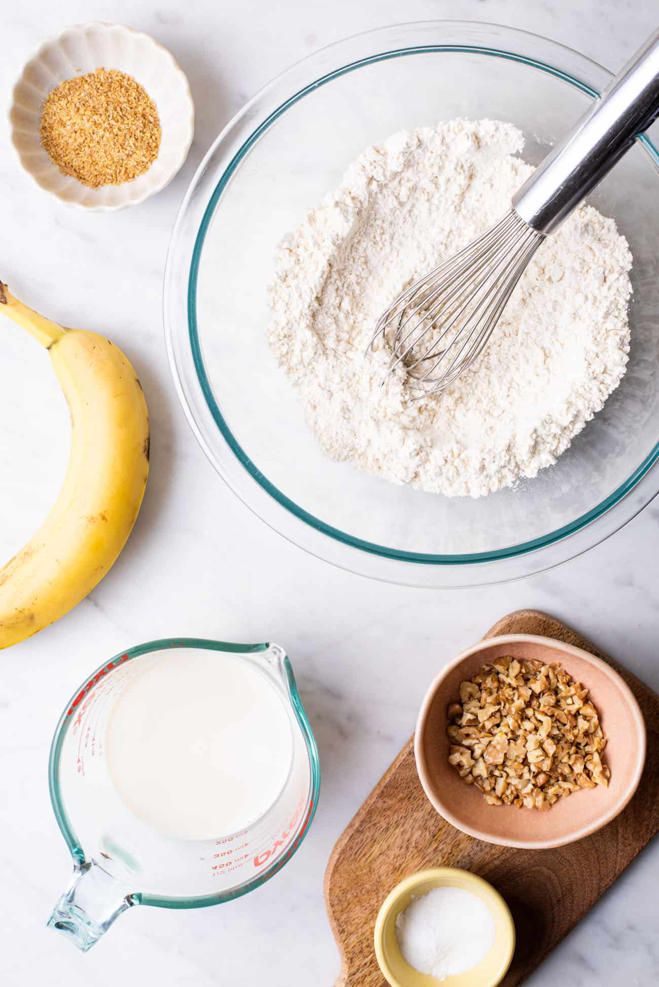 Ingredients gathered to make banana walnut pancakes on a marble counter