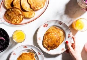 Banana walnut pancakes on a sunny table, next to glasses of orange juice, and blueberry chia jam