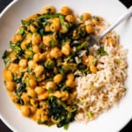 A white bowl of chickpea spinach curry with basmati rice.