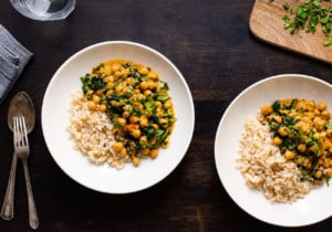 Two bowls of chickpea spinach curry on a dark wooden table.